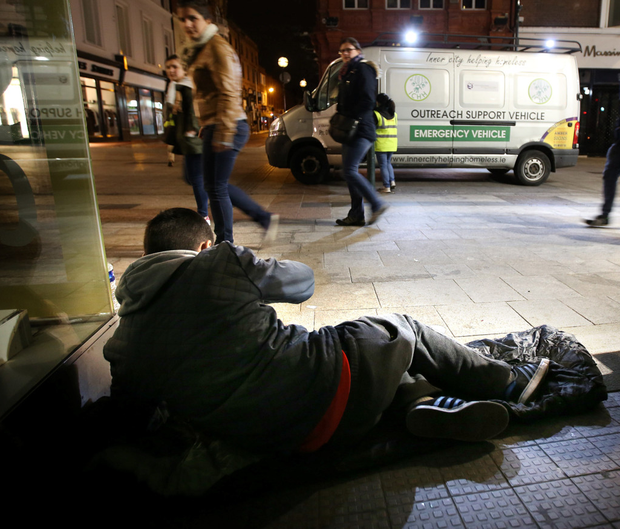 People pass someone sleeping rough in Dublin city centre