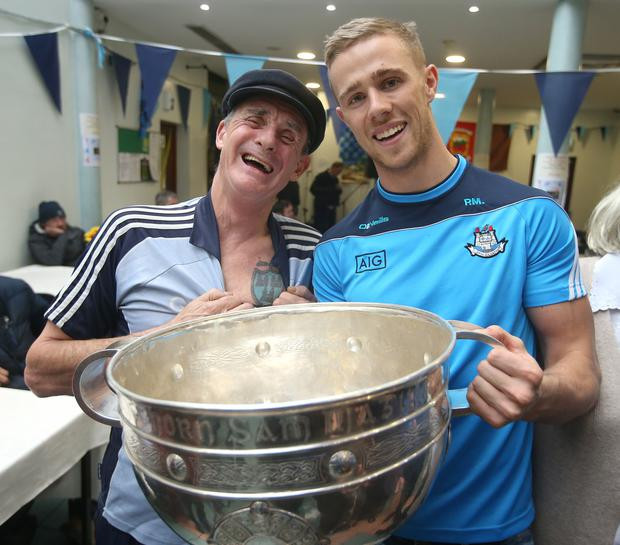 Dublin player, Paul Mannion, and Joseph Deegan, shiowing his dublin tatoo, hold the Sam Maguire Cup during a visit to the Capuchin Day Centre for the homeless in Dublin