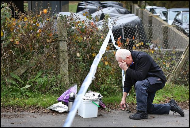 A relative kneels and prays at the sealed off road in Knockadoon outside Tom and Kitty Fitzgerald's home where their bodies were discovered.