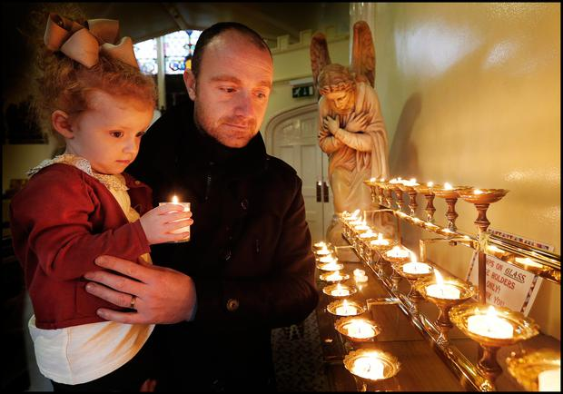 Stuart O'Donnell and his daughter Millie (3) light a candle for his brother Wayne at St Michan's Church