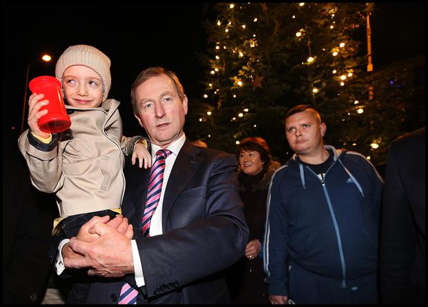 Taoiseach Enda Kenny holds Evan O'Brien (6) from Beaver Street at the Annual Lighting of the Christmas Tree on Buckingham Street last night.