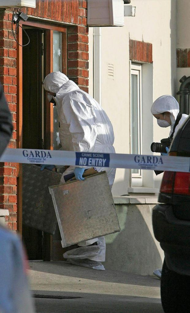 Gardai enter the house in Finglas, where Anthony Campbell and Hyland were shot dead