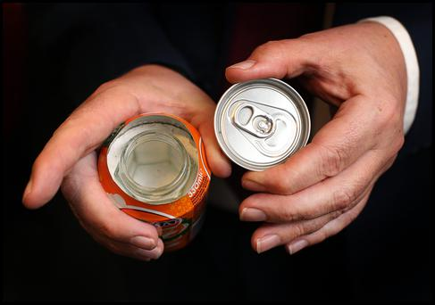 A Customs officer at Dublin Airport with a fake soft drinks can which has a screw off top with hidden compartment for drugs.