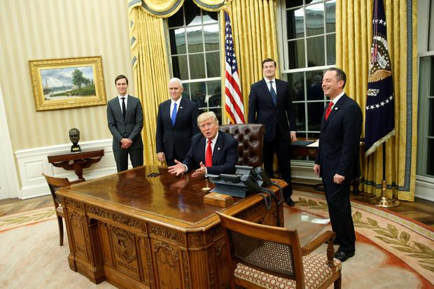 President Trump welcomes reporters into the Oval Office for him to sign his first executive orders at the White House Picture: Reuters