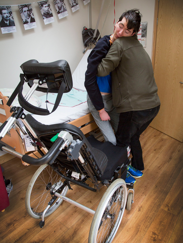 Rheinhard Schaler pictured helping his his son Padraig (26), who suffers from a brain injury and is on a waiting list for Rehab, to his wheelchair at their Glasnevin Home yesterday