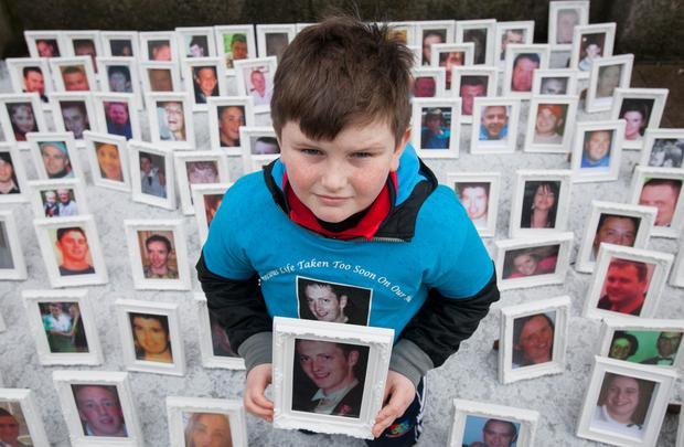 David Gibbons (8) with a photo of his father James, who was killed on the roads in 2008, during the vigil in Dublin