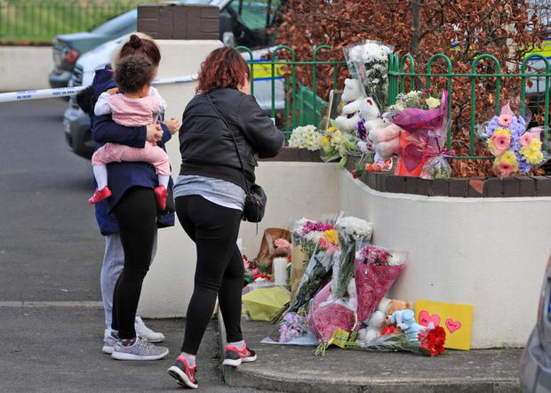 Neighbours place flowers in Kilcronan Avenue, Clondalkin, where a woman and three children died. Photo: Collins