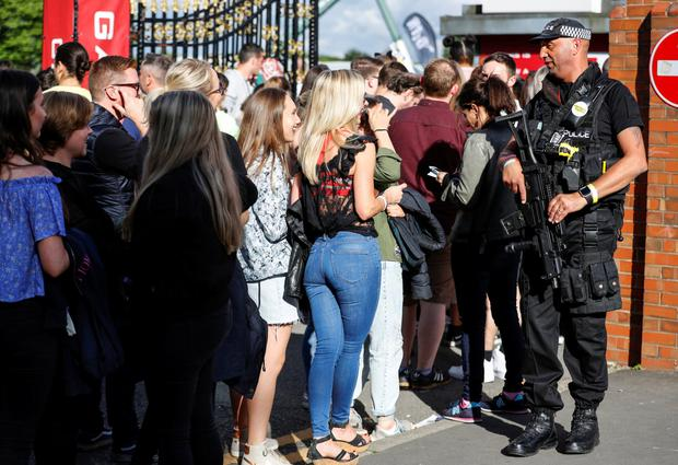 An armed policeman is seen with music fans at the One Love Manchester concert in Manchester, Britain, June 4, 2017. REUTERS/Phil Noble