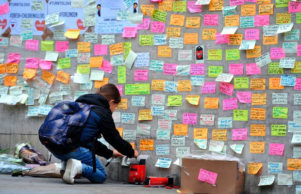 A young girl leaves a message of support on the base of the obelisk on London Bridge, after an unknown 21 year-old man left a box of tape, sticky notes and marker pens with an invite to write a message, following the terror attack in which eight people died. Photo: Nick Ansell/PA Wire