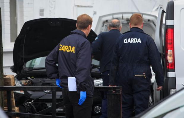 CAB officials and gardai search cars at a Dublin dealership as part of a crackdown on 'The Family' drugs gang