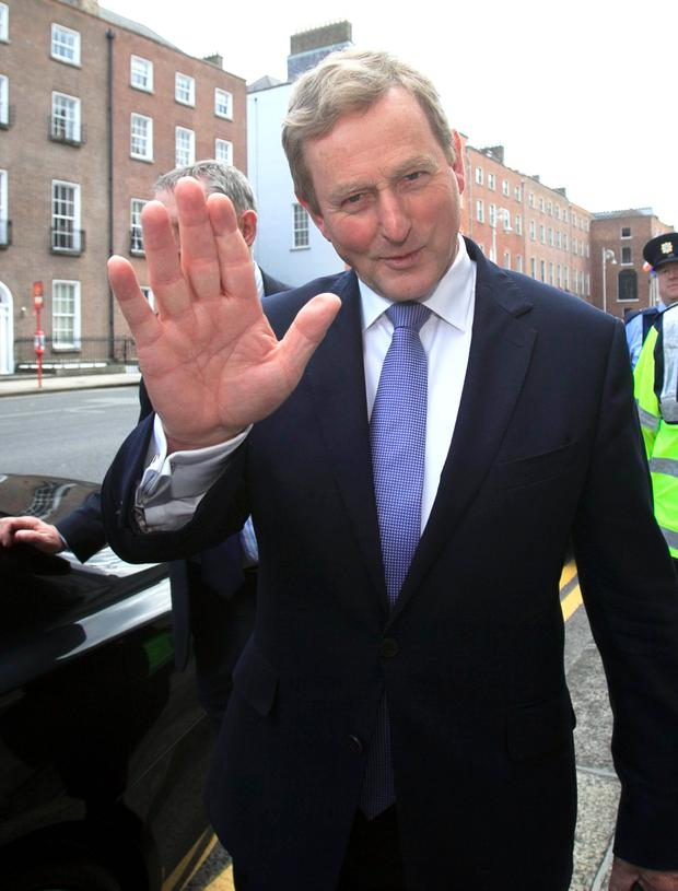 Enda Kenny waves as he leaves the Dail to travel to Aras an Uachtarain to tender his resignation. Photo: Collins