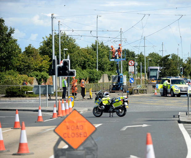Workers carry out repairs to Luas overhead lines as gardai redirect traffic on the Belgard road junction