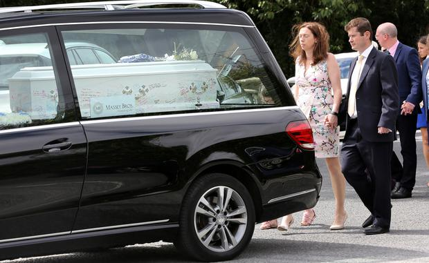 Mourners, including Cian's parents, follow his coffin adorned with messages from family and friends