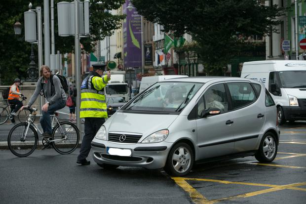 A garda stops a motorist from turning right on to O'Connell Bridge after the changes to the traffic flow were made