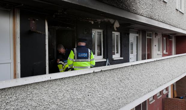 Gardai examine Maggie Green's flat in Inchicore after a fire left her and her son Francie (8) in a critical condition