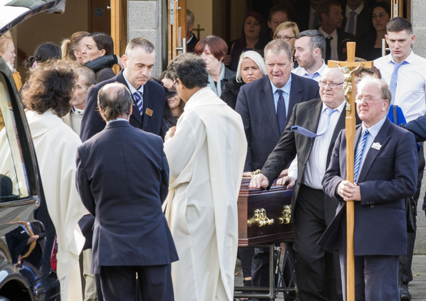 Mourners and family members leave the church in Rowlagh after the funeral service