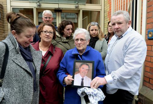 Ellen Hackett holding a photo of her late husband John Hackett, surrounded by her family, after the inquest into his death. Coroner's Court, Store Street, Dublin. Picture: Caroline Quinn