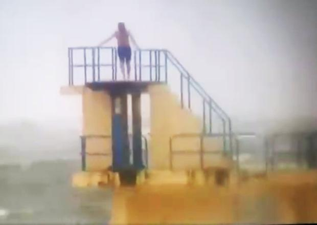 People swim during the storm