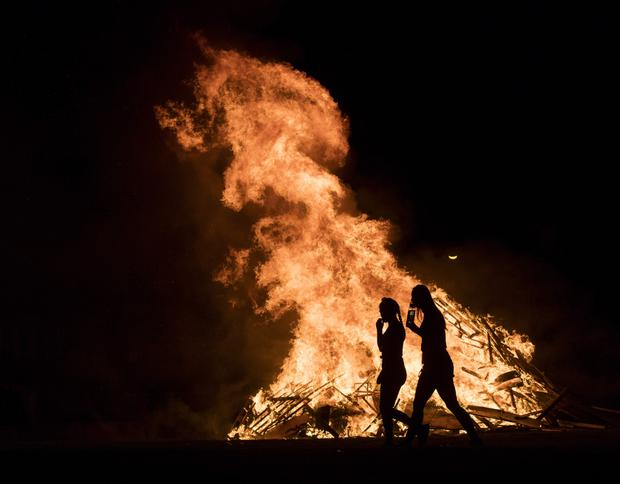 Young people pass a Halloween bonfire in Darndale. Photo: Arthur Carron