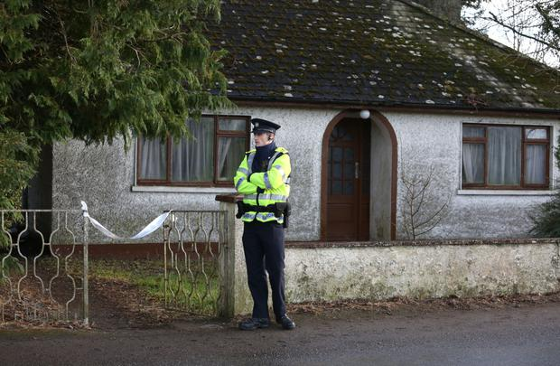 A Garda outside the home of Mr Waters. Photo: INM