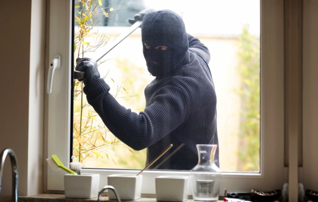A burglar breaking into a home