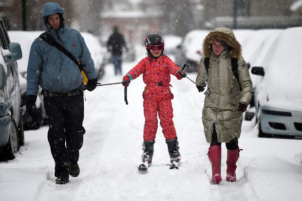 Parents in Dublin use skis to go for a walk with their child