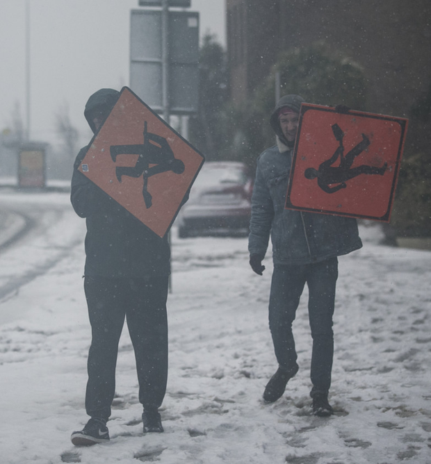 Two men making their way to Blackrock use signs to shield themselves from the blinding wind