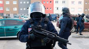 A masked member of the specialist GIGN police at the siege scene. Photo: AFP/Getty Images