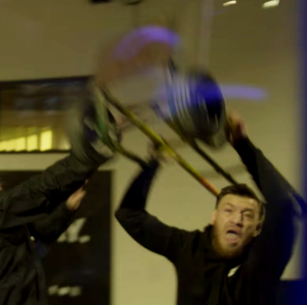 Conor McGregor hurls a trolley at the bus as one of his entourage tries to stop him