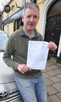 Brian Kelly outside his pub with his car and insurance quote