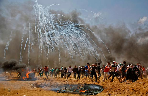 Palestinians run for cover from tear gas. Photo: AFP/Getty Images