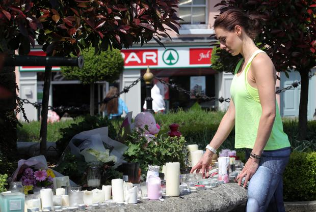 A woman looks at the floral tributes to Jastine in Enniskerry