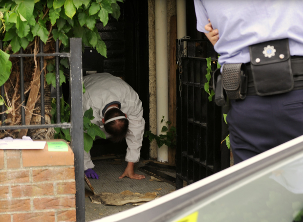 Forensic gardai access the uncovered drugs lab through a hole in the front door.