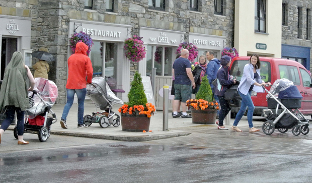 Pedestrians are caught in a downpour in Westport, Co Mayo, yesterday
