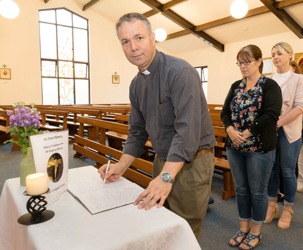St Senan's parish priest Fr Arnie Rosney signs a book of condolence for the late Brian O'Callaghan-Westropp at SS John and Paul Church, Shannon