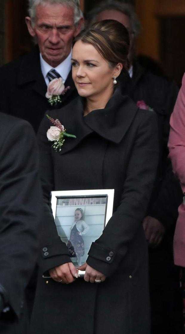 Eileen Loughlin carries a picture of daughter Annabel at her funeral