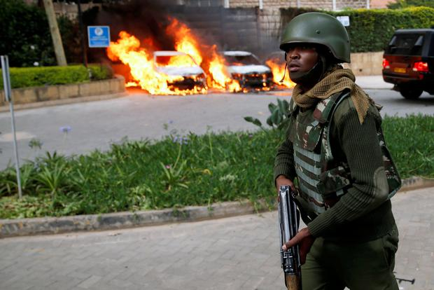 A member of the Kenyan security forces runs past burning cars at the scene close to an upscale Nairobi hotel compound