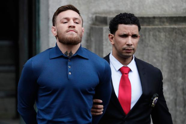 McGregor is led out of the 78th Police Precinct in the Brooklyn borough of New York in April last year after his arrest for the bus trolley attack