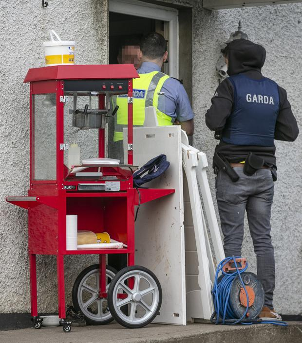 Gardai speak with a man at the door of the property