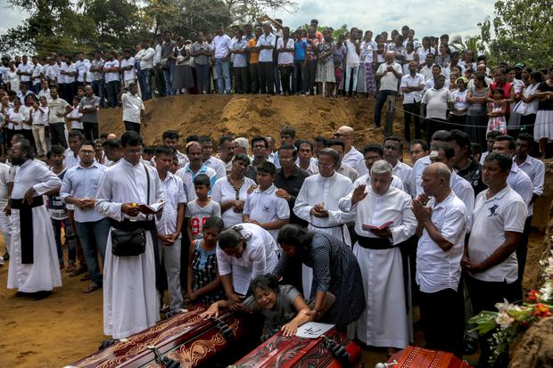 A woman is pulled from two coffins in a funeral Mass in Sri Lanka. Photo: Reuters/Athit Perawongmetha