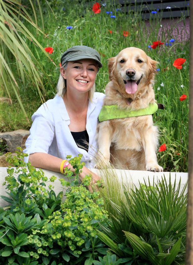 Designer Grainne Walsh in her garden with assistance dog Farah