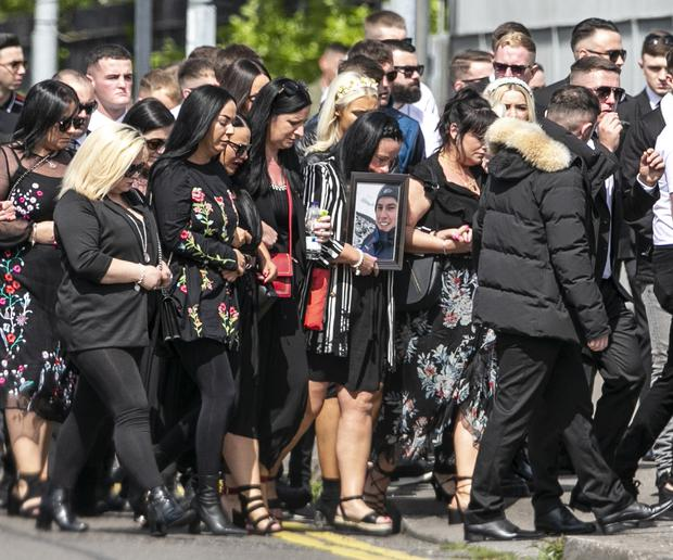 Mourners carry a photograph of gun victim Sean Little