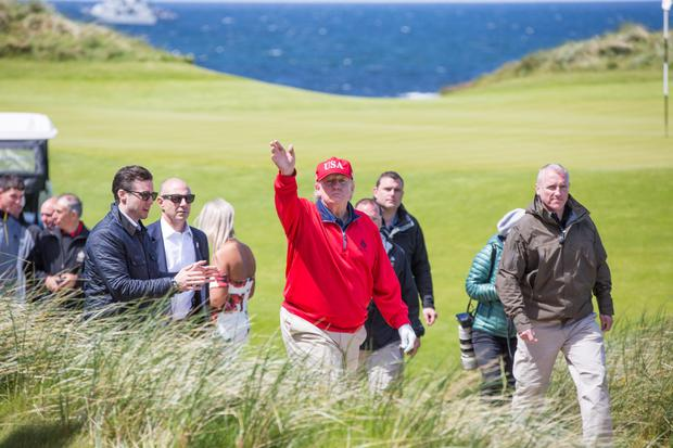 US President Donald Trump waves to crowds after finishing a round of golf at his Doonbeg course during last week's visit