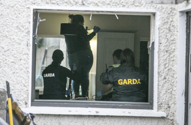 Garda officers search the property that was raided in Finglas