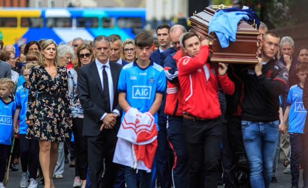 John Bailey's coffin is carried by Tanaiste Simon Coveney and Dublin star Con O'Callaghan at his removal in Dalkey