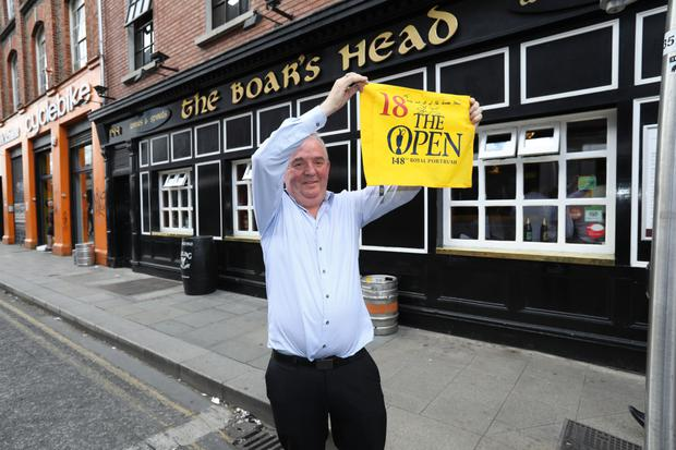 Pub owner Hugh Hourican shows off the signed 18th hole flag