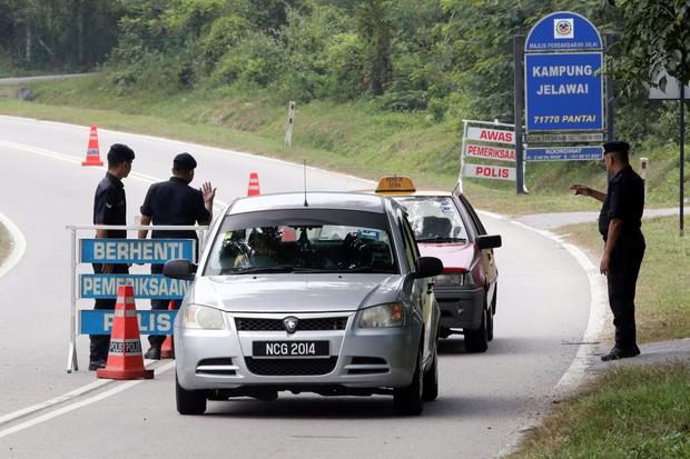 Malaysian police stop vehicles at a checkpoint near the resort where Nora went missing