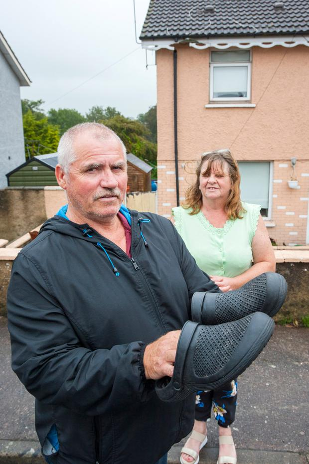 Terence and Jacqueline Alcock at their home in Cobh with the rubber clogs Terence says saved his life. Photo: Daragh McSweeney