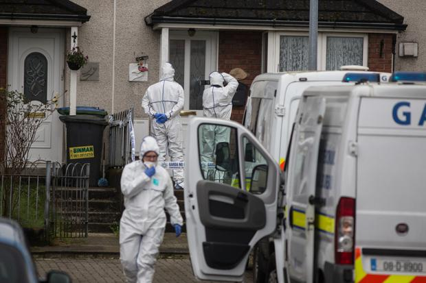 Forensic officers begin an examination of the property