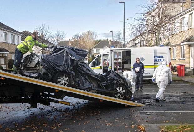 The burnt-out wreckage of the car in                             which the man's body was found is removed                             from scene